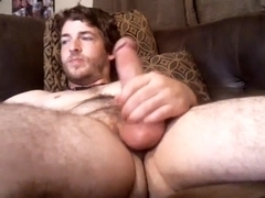 Seductive gay is having a good time in the apartment and memorializing himself on computer webcam
