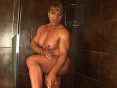 Big bodybuilder rubs her big sexy muscles as she takes a hot shower