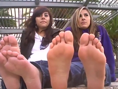 Two sweet college students in jeans sitting barefoot in public and they enjoying it
