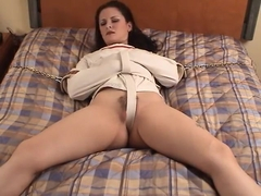 Angry woman struggling in straitjacket bed bondage