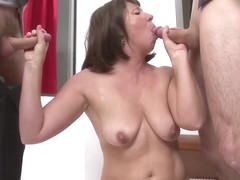 Mature woman is satisfying two younger guys at the same time with her lips and pussy