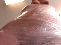 Mistress wraps female slave in cling film
