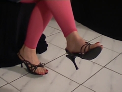 Sexy female feet tapping in black sandals