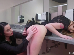 Brunette spanks blonde slave in restroom