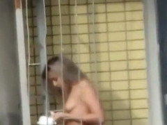 Voyeur films topless chick in the balcony