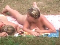 Topless tanning women in the park