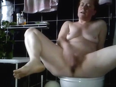 Horny mature lady rubbing her pussy really hard on the toilet