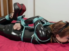 Mina tied in a PVC catsuit