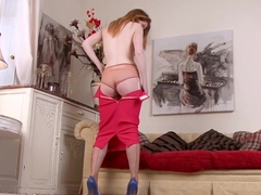 Mature, red haired woman is wearing stockings while spreading up to play with her pussy