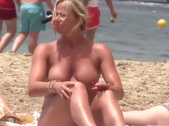 Stunning Milf shows off her big tits on the beach