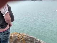 Zoey masturbating in public high on a rock in the harbor