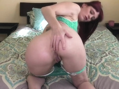Redhead plays with her ass while talking dirty