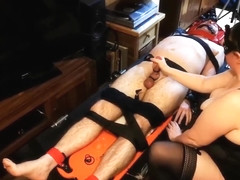 Man fully restrained, enjoying penis and ball torture from two mistresses
