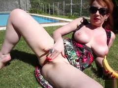 Red XXX stuffs her mature pussy with a banana outdoors