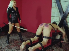 Blonde mistress caning her slave