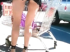 Exhibitionist woman in short skirt bent over