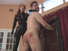 Slave gets caned by a redhead dominatrix