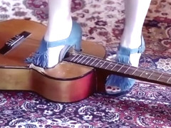 Girl crushing a guitar in high heels