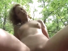 Cock loving blonde is giving a blowjob to a stranger in a local forest, during the day